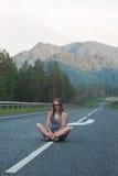 Frau, die auf der Straße sitzt Stockfotografie