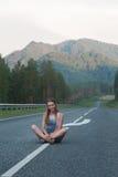 Frau, die auf der Straße sitzt Lizenzfreie Stockfotos