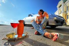 Frau, die auf der Straße sitzt stockfoto