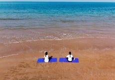 Frau, die auf der Strandantenne meditiert lizenzfreie stockfotos