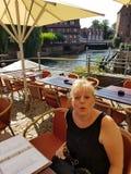 Frau, die auf der Terrasse eines Restaurants in Lueneburg sitzt lizenzfreie stockbilder