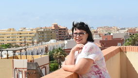 Frau, die auf der Terrasse steht und das Meer betrachtet stock footage
