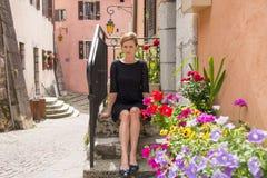Frau, die auf der Treppe mit Blumen sitzt Stockbild