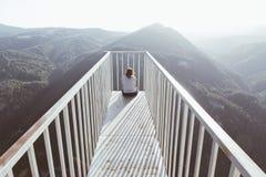 Frau, die auf der verschobenen Plattform genießt Berg sitzt Stockbilder