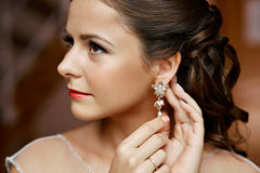 Frau, die auf Diamantohrringe sich setzt kaukasisch stockfotos