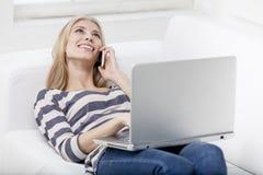 Frau, die auf die Couch mit Laptop legt Lizenzfreie Stockfotos