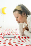 Frau, die auf digitaler Tablette auf ihrem Bett schaut Stockbilder