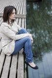Frau, die auf Dock nahe Wasser sitzt Lizenzfreies Stockbild