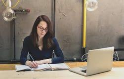 Frau, die auf ein Papiernotizbuch studiert und schreibt Stockfotos