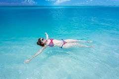 Frau, die auf eine Rückseite im schönen Meer schwimmt Stockfotografie