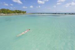 Frau, die auf eine Rückseite im schönen Meer schwimmt Lizenzfreies Stockbild