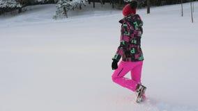 Frau, die auf eine Schneewehe im Winter auf dem Gebiet geht stock video footage