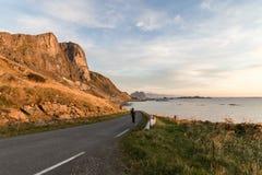 Frau, die auf eine Straße in Lofoten geht Stockfoto