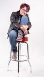 Frau, die auf einem alte Schulbarhocker sitzt Lizenzfreies Stockfoto