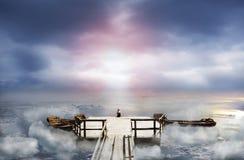 Frau, die auf einem alten Pier im Himmel sitzt Stockfotografie