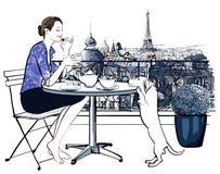 Frau, die auf einem Balkon in Paris frühstückt Stockfotografie