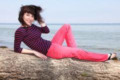 Frau, die auf einem Baum auf einem sonnigen Strand stillsteht Lizenzfreies Stockbild