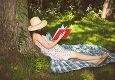Frau, die auf einem Baum draußen liest ein Buch sich entspannt Lizenzfreies Stockbild