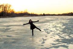 Frau, die auf einem Bein auf dem Eis auf dem gefrorenen Platte River im Winter bei Sonnenuntergang steht Stockbild
