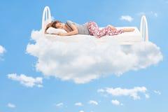 Frau, die auf einem bequemen Bett in den Wolken schläft Stockbild