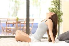 Frau, die auf einem Bett atmet und sitzt Lizenzfreie Stockfotografie