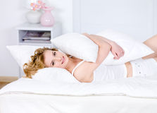 Frau, die auf einem Bett im Morgen sich entspannt Stockbilder