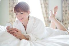 Frau, die auf einem Bett mit Handy liegt Stockbilder