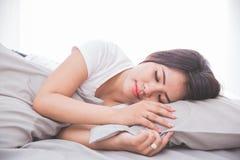Frau, die auf einem Bett schläft Lizenzfreie Stockfotografie
