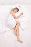 Frau, die auf einem Bett schläft Lizenzfreies Stockfoto