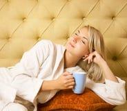 Frau, die auf einem Bett sitzt Lizenzfreie Stockfotografie