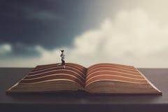 Frau, die auf einem Buch läuft Lizenzfreie Stockfotos