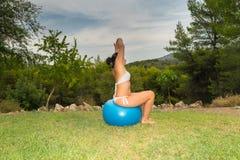 Frau, die auf einem Eignungsball heraus ausdehnt ihren Körper sitzt Stockfotografie