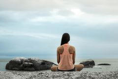 Frau, die auf einem Felsen bei Sonnenuntergang auf Bakovern-Strand, Cape Town meditiert stockfotos
