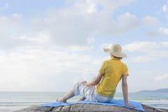 Frau, die auf einem Felsen in dem Meer sitzt stockfotografie