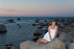 Frau, die auf einem Felsen durch das Meer sitzt Lizenzfreie Stockfotos