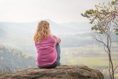 Frau, die auf einem Felsen erwägt Stockfotografie