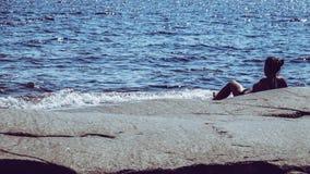 Frau, die auf einem Felsen im Ozean heraus betrachtet dem Horizont liegt stockfotografie