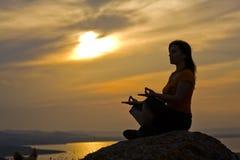 Frau, die auf einem Felsen meditiert Lizenzfreie Stockfotos