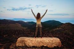 Frau, die auf einem Felsen mit ihren Armen oben steht Stockbild