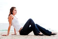 Frau, die auf einem Felsen sitzt Stockbild