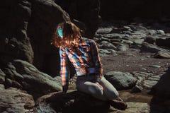 Frau, die auf einem Felsen sitzt Lizenzfreie Stockbilder