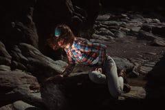 Frau, die auf einem Felsen sitzt Lizenzfreies Stockbild