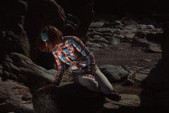 Frau, die auf einem Felsen sitzt Stockfotografie