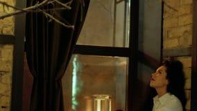 Frau, die auf einem Fensterbrett sitzt stock video footage