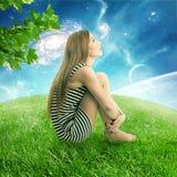 Frau, die an auf einem grünen Wiesenerdplaneten oben betrachtet sternenklarem Himmel sitzt Stockbilder