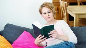 Frau, die auf einem grauen Sofa sitzt und ein Buch liest stock video