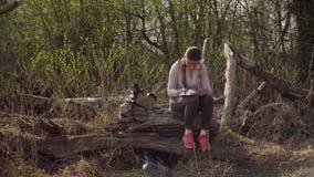 Frau, die auf einem großen gefallenen Baum sitzt und in ein Tagebuch schreibt stock video