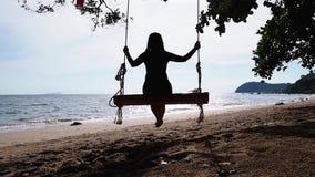 Frau, die auf einem hölzernen Schwingen am Sonnenuntergangstrand schwingt stock video