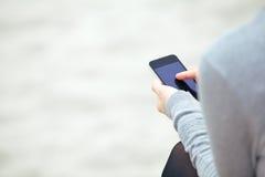 Frau, die auf einem Handy texting ist Lizenzfreie Stockbilder