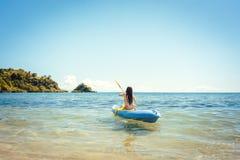 Frau, die auf einem Kajak auf Meer im klaren Wasser schaufelt Stockfoto